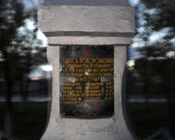 """Надпись: """"Здесь похоронены коммунисты, погибшие от рук кулаков во время кулацкго восстания в 1921 году. Беккер Н.Г., Борш Н.Н., Волде И.Н., Гассман А., Госниц И., Герман Т.И., Зальцман В.Е., Кеслер И.И., Сандер Н.И., Штерцер П.П., Шуллер И.Я."""""""